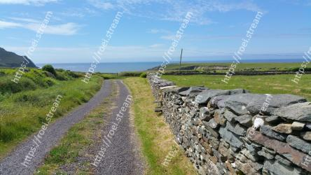 Wall,Stone wall,Raised beach,Rock,Coast,Sea,Road,Grass,Fell,Landscape