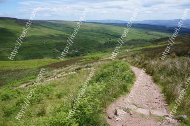 Highland,Mountainous landforms,Grassland,Hill,Dirt road,Mountain,Natural landscape,Fell,Trail,Road